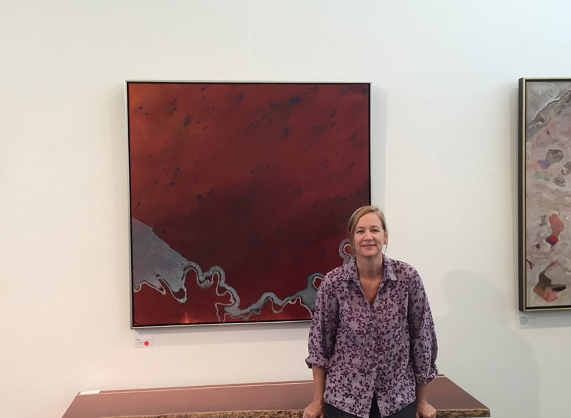 "Bec Juniper in front of ""Sideways River"" painting"