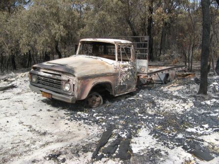 Dodge Truck sitting in the ash laden sand and very sad looking bush behind